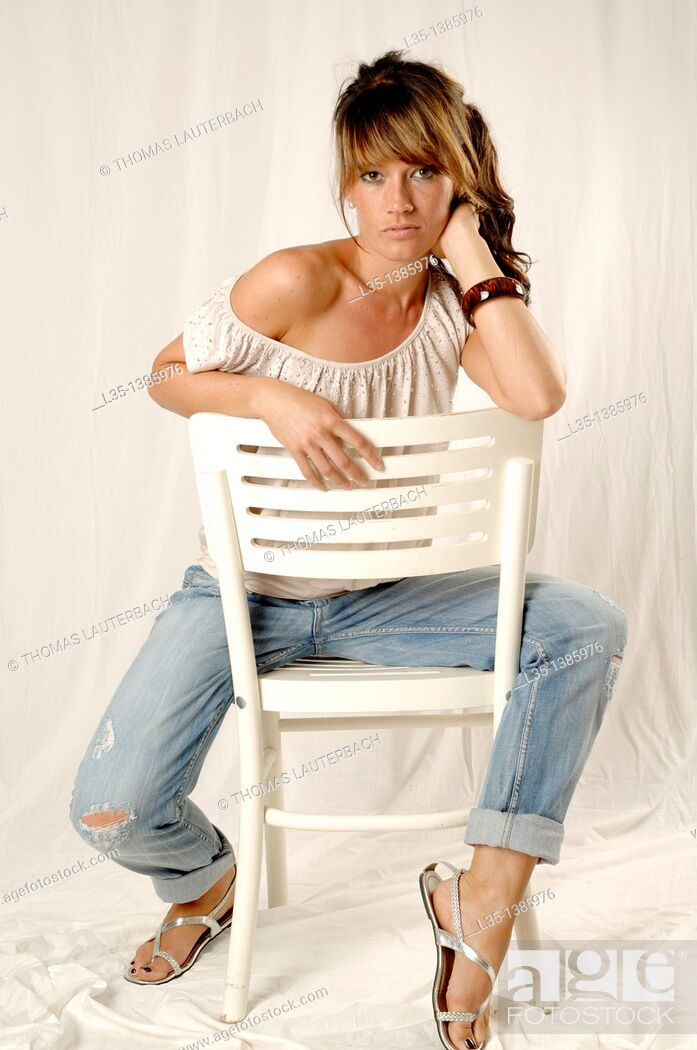 Stock Photo: Young woman on a white chair in the studio.