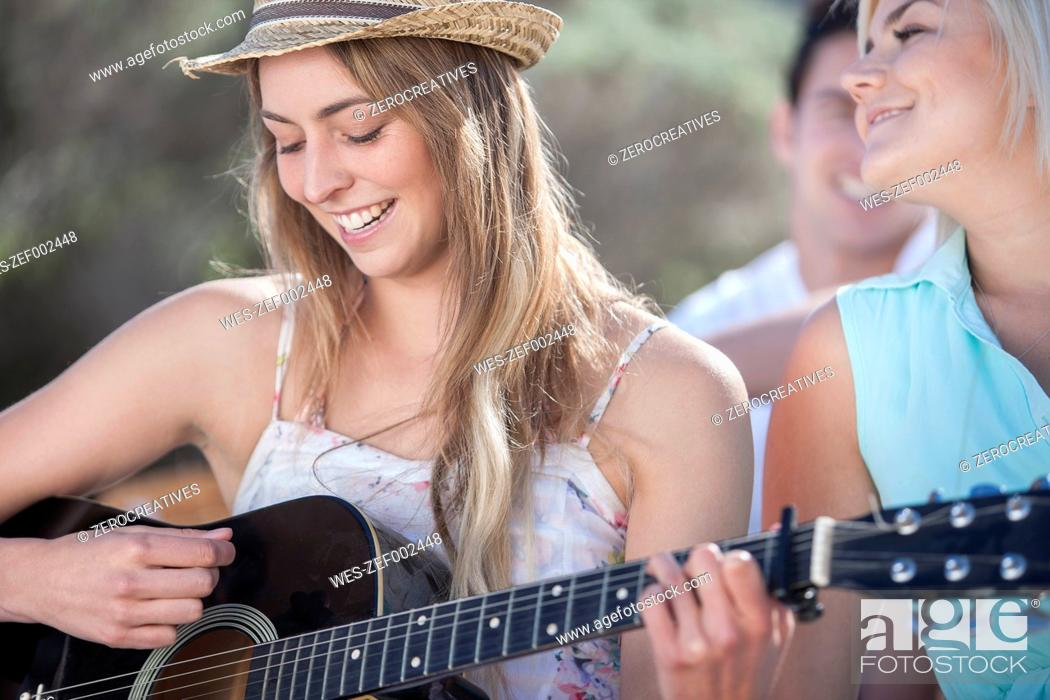 Stock Photo: Happy friends with guitar outdoors.