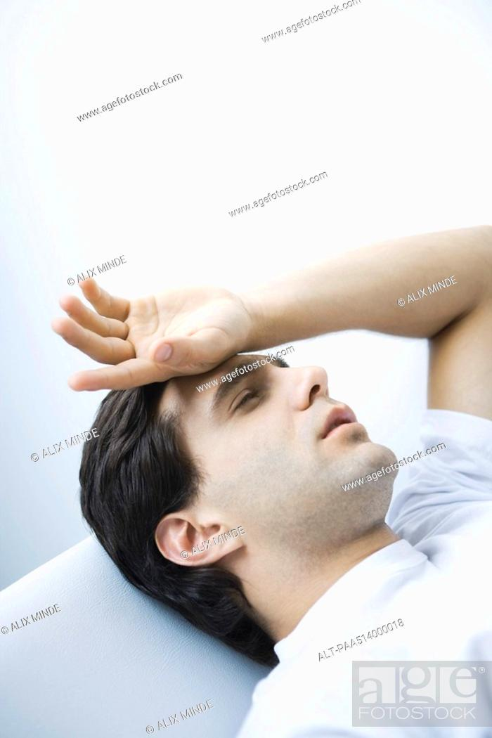 Stock Photo: Man reclining with eyes closed, hand on forehead.