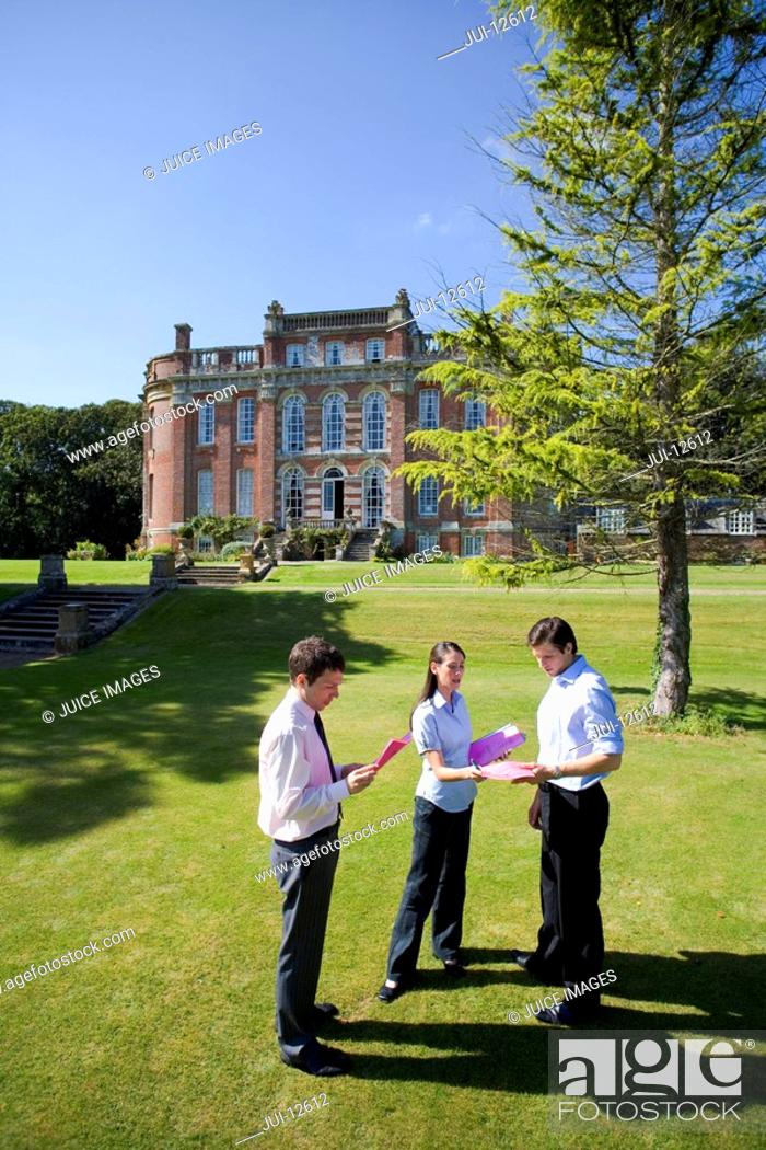 Stock Photo: Young businesswoman giving man folder by manor house, elevated view.