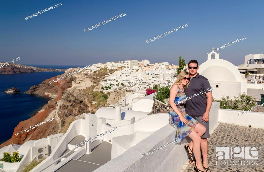 Stock Photo: A couple posing together on a white wall on a greek island with the town in the background; Santorini, Greece.