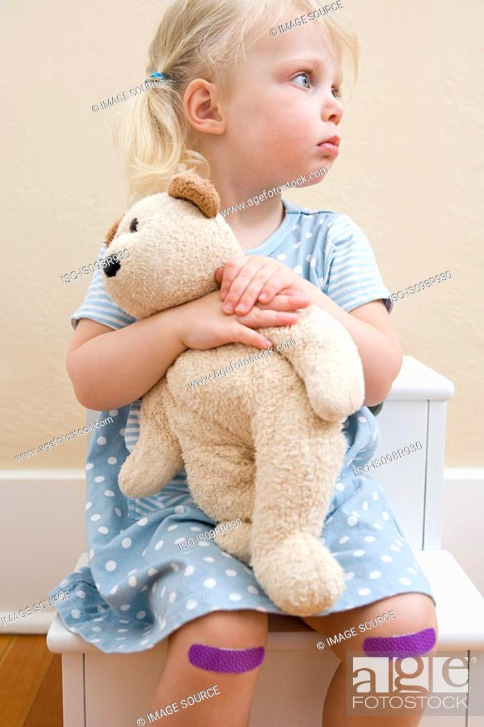 Stock Photo: Girl with teddy bear and plasters on knees.