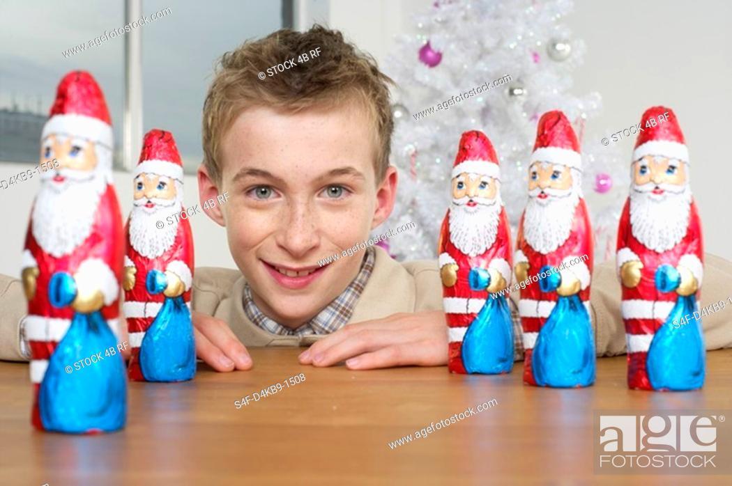 Stock Photo: Boy smiling at camera, Santa Claus chocolates on a table.
