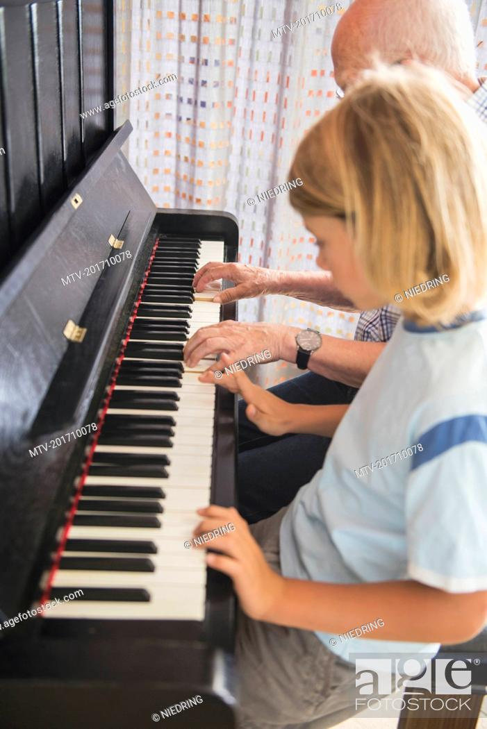 Photo de stock: Grandfather and grandson playing piano instrument.