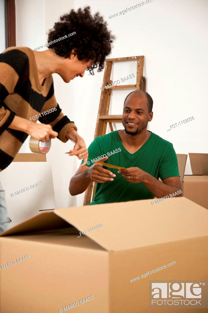 Stock Photo: A cheerful couple working together to tape a moving box.