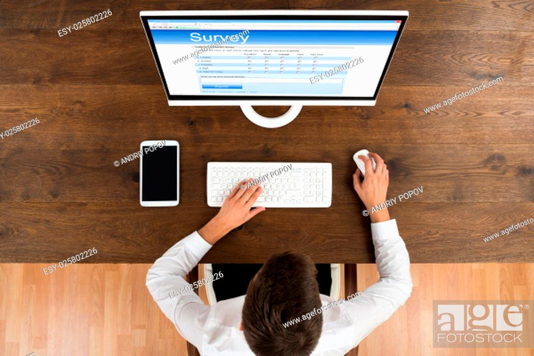 Stock Photo: High Angle Of Young Businessman Filling Online Survey Form On Computer.