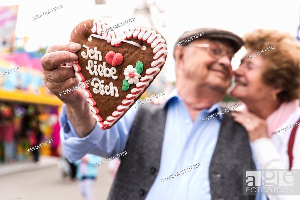 Stock Photo: Hand of senior man holding ingerbread heart on fair, close-up.