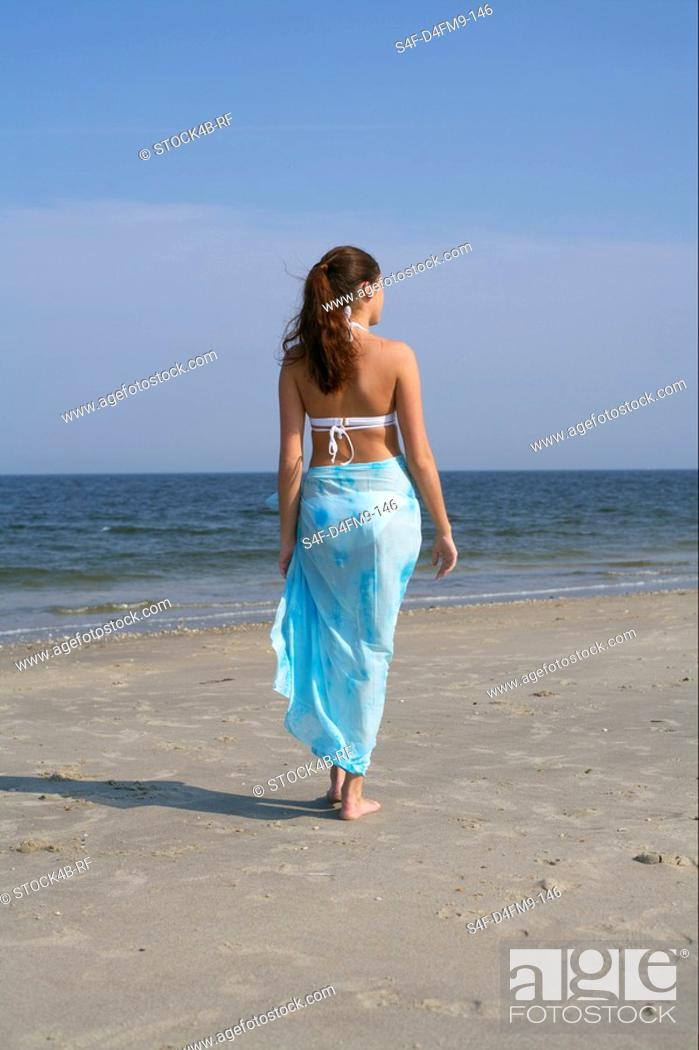 Stock Photo: Young brunette woman promenading at the beach.