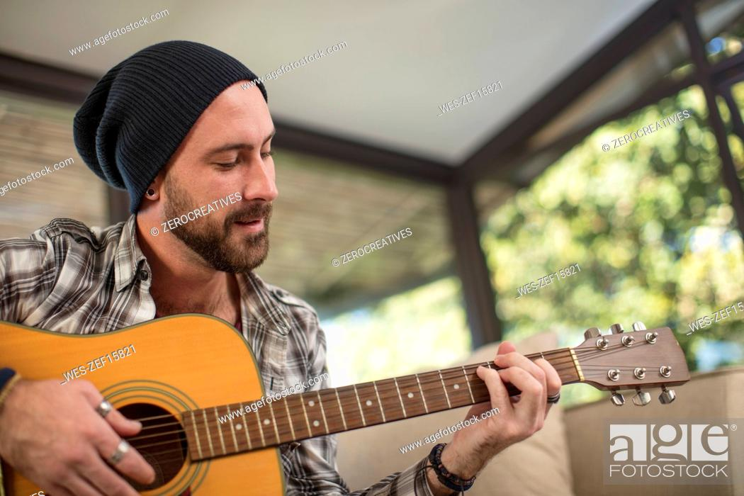 Imagen: Young man at home sitting on couch playing guitar.