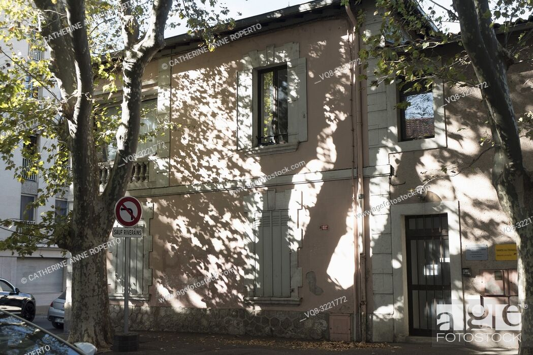 Stock Photo: Plane trees cast dramatic shadows and reflections on a traditional pink and white shuttered house behind a residents only road sign in Avignon, Vaucluse.