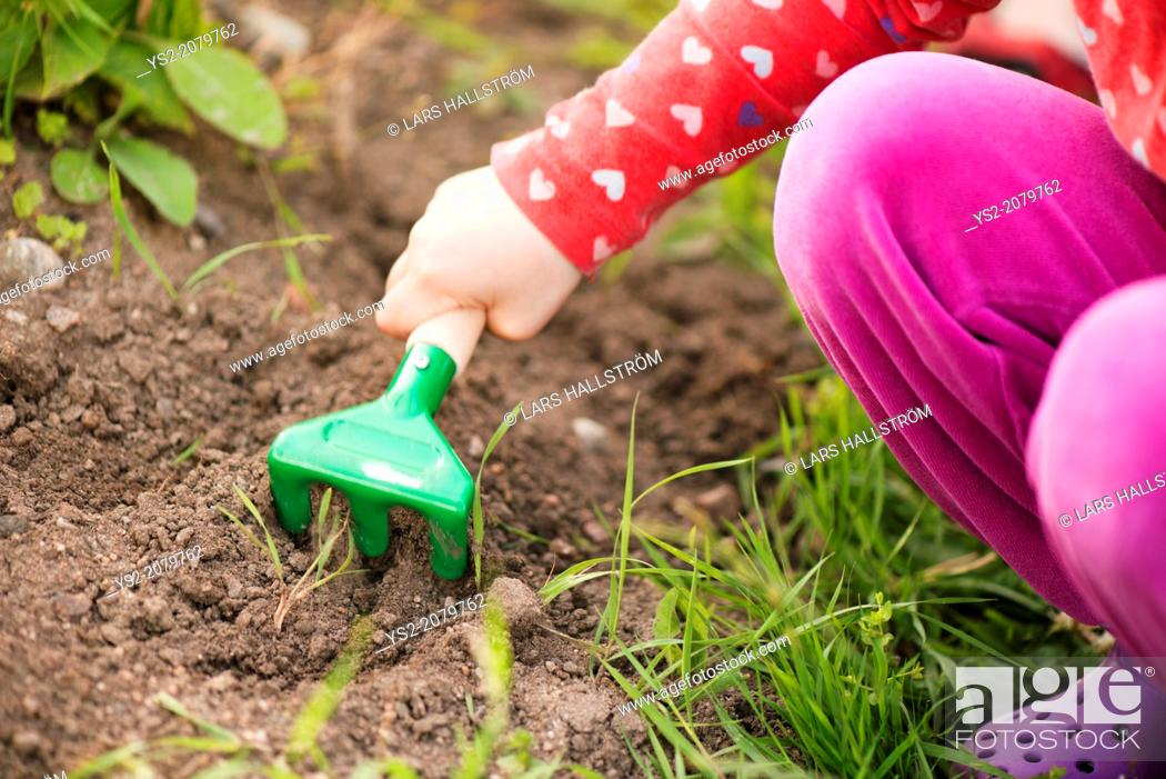 Stock Photo: Close up of young child in garden helping with plants and flowers, digging in the soil.