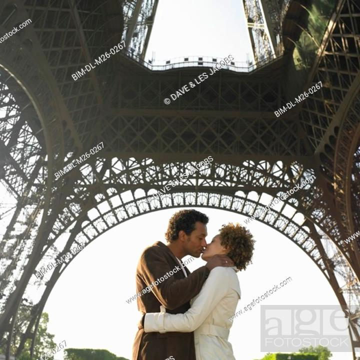 Stock Photo: Couple kissing under Eiffel Tower.