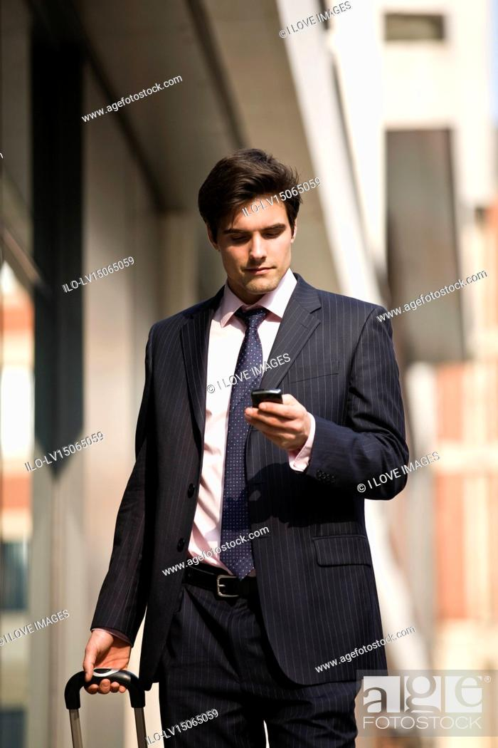 Stock Photo: A businessman pulling a suitcase, using his mobile phone.