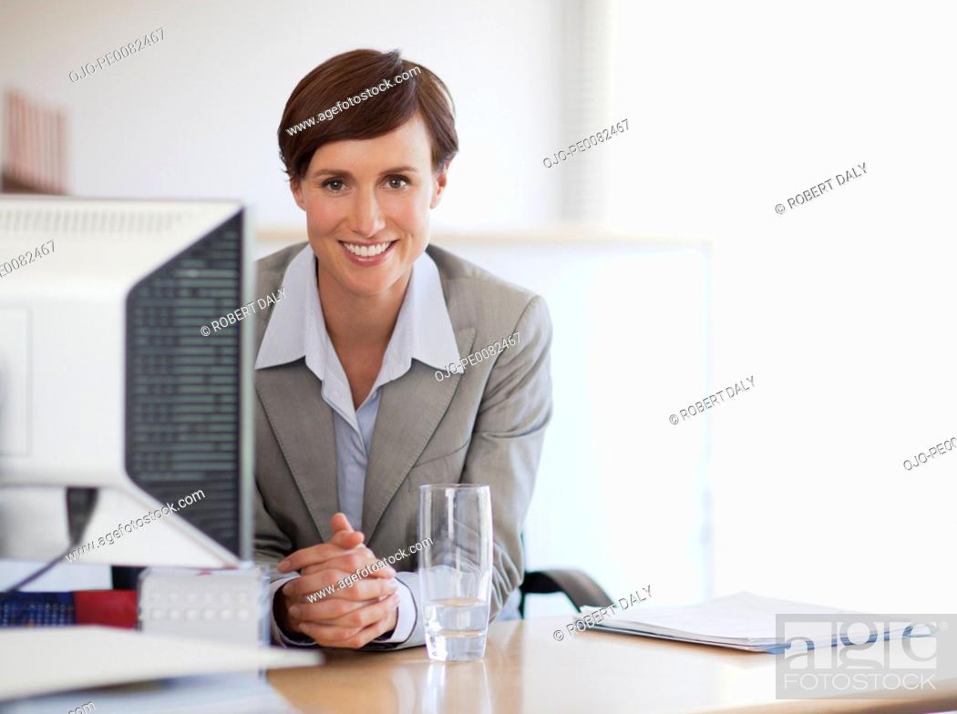Stock Photo: Portrait of smiling businesswoman at desk in office.