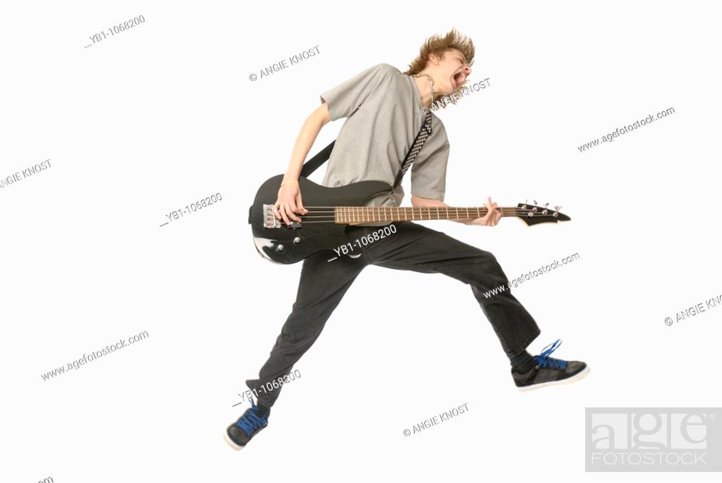Stock Photo: Teenage boy jumping in while playing bass guitar.