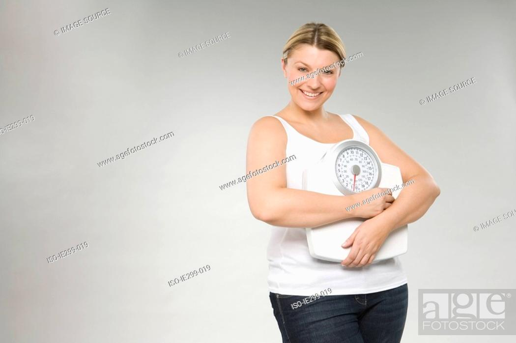 Stock Photo: A woman holding weight scales.