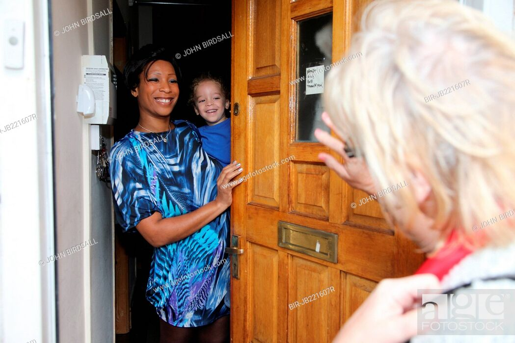 Stock Photo: Mother and toddler at doorway greeting visitor.