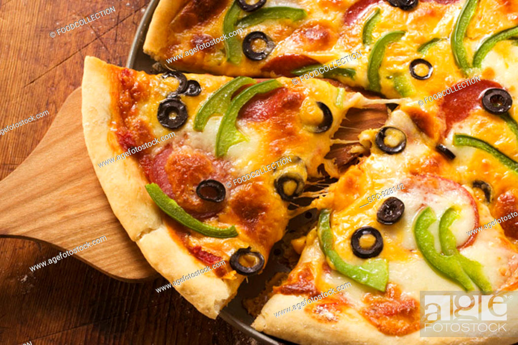 Stock Photo: Pizza with cheese, salami, peppers and olives, pieces cut.
