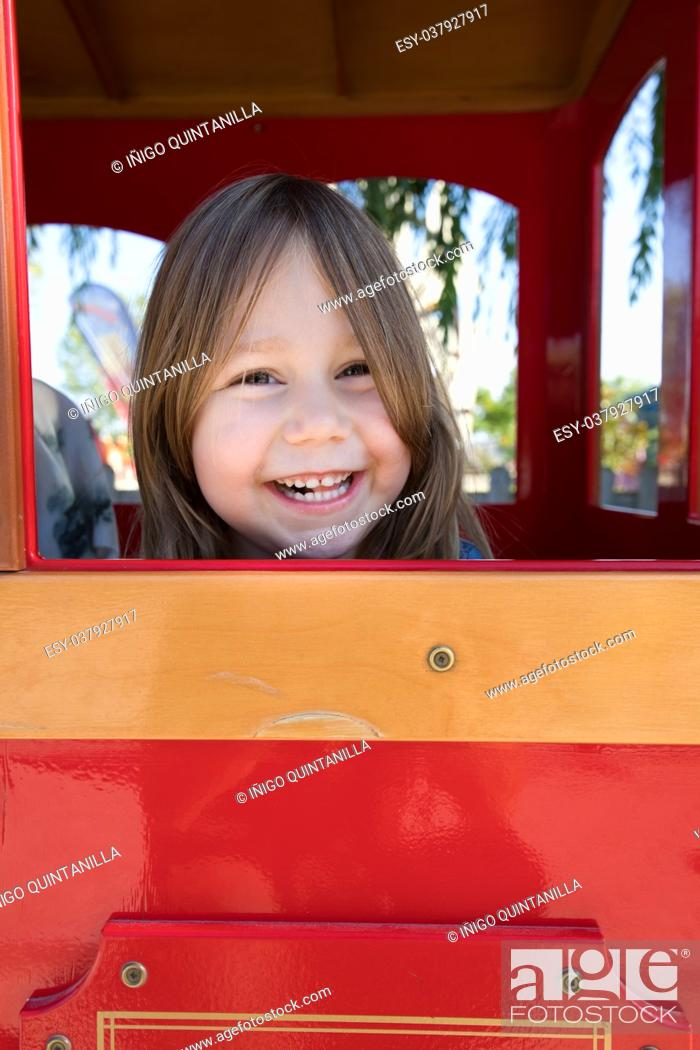 Imagen: face of four years old blonde girl looking and laughing from the window of playground house in public park.