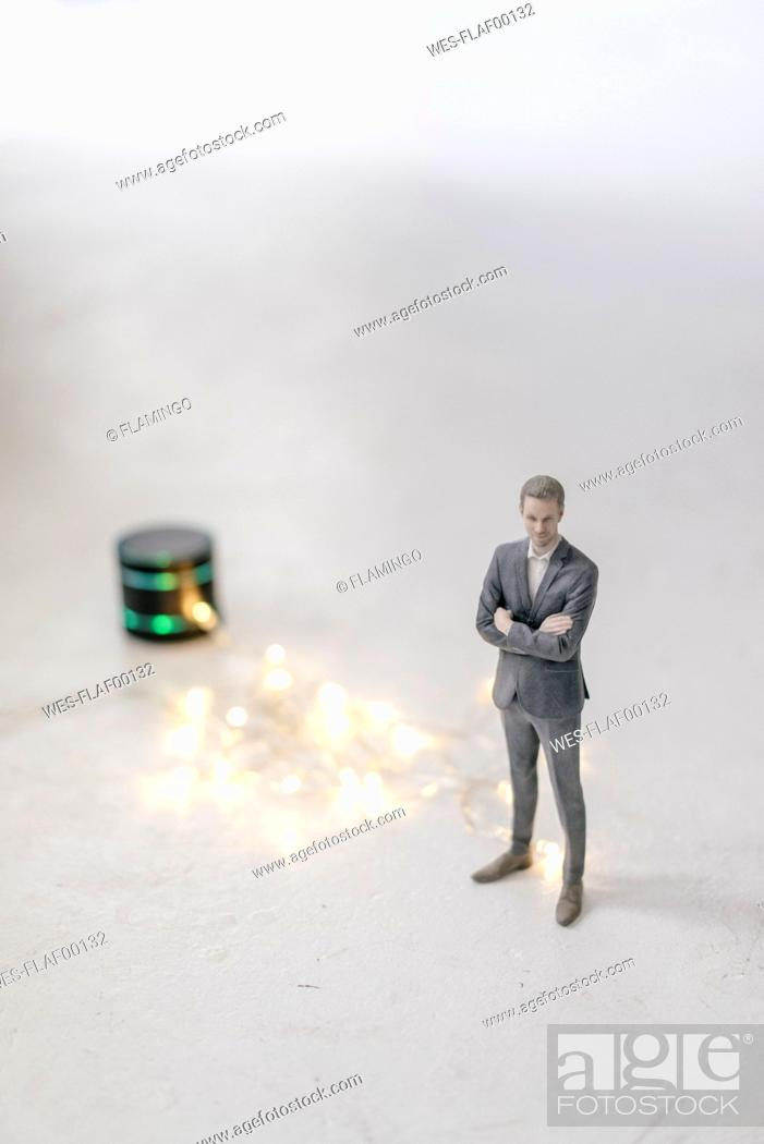 Stock Photo: Miniature businessman figurine standing next to smart home loudspeaker with chain of lights.