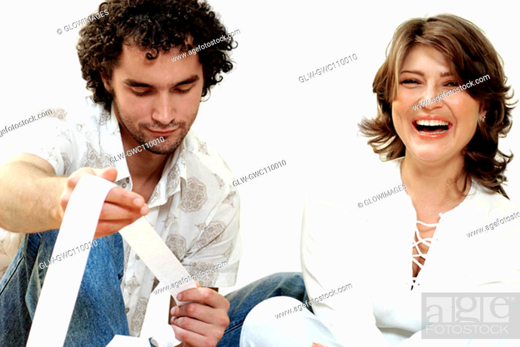 Stock Photo: Portrait of a young woman laughing with a young man looking at a receipt.