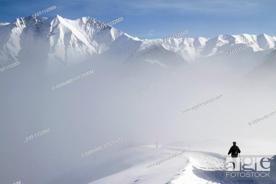 Stock Photo: Hiking on trail by snowy mountain range.