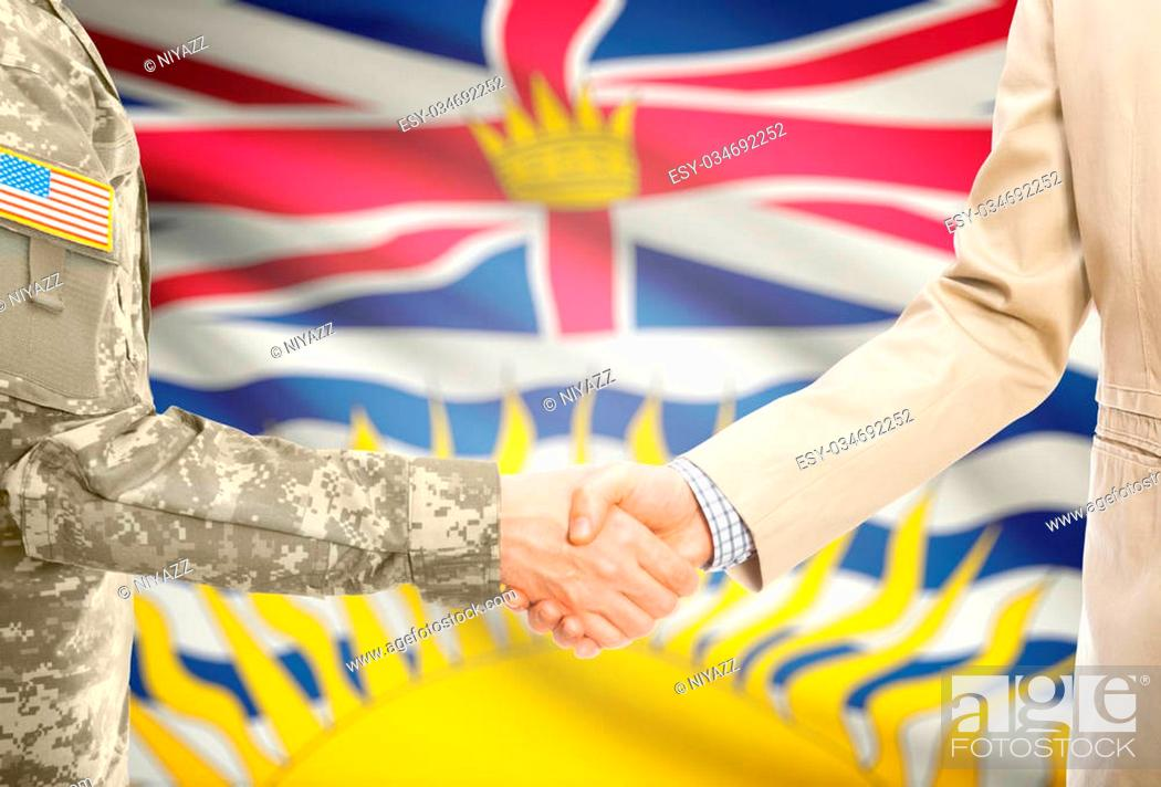 Stock Photo: American soldier in uniform and civil man in suit shaking hands with Canadian province flag on background - British Columbia.