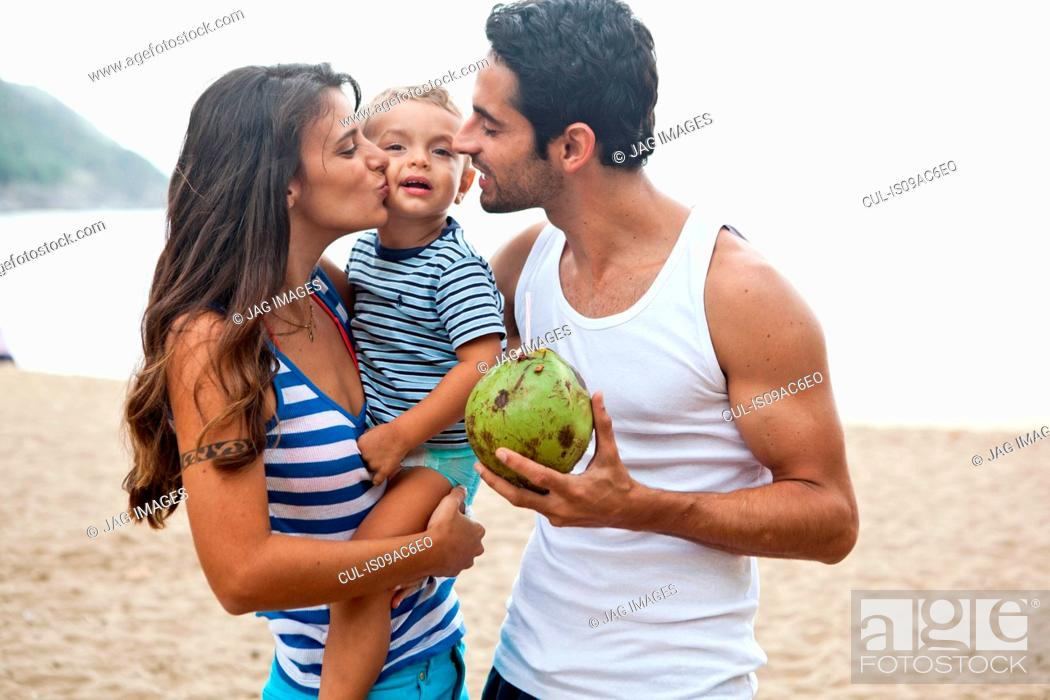 Stock Photo: Family on beach, mother kissing son on cheek.