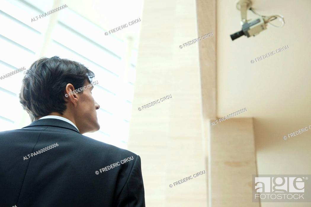 Stock Photo: Businessman looking up at security camera.