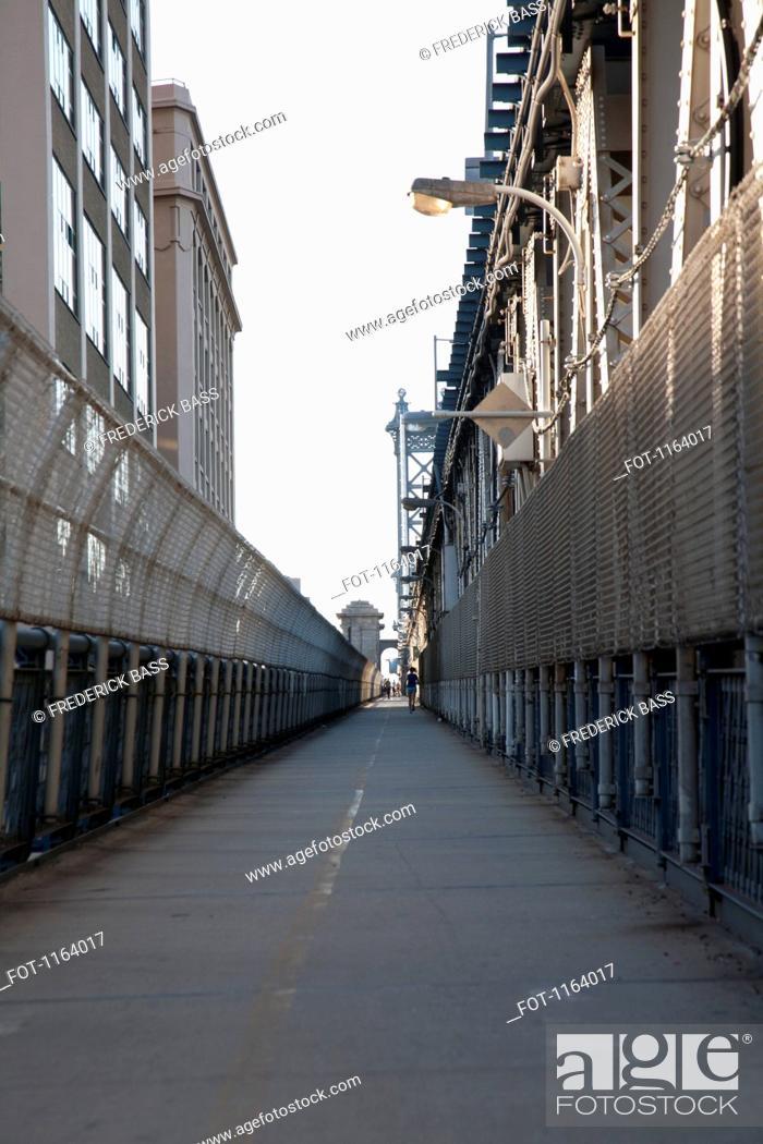 Stock Photo: Jogger on pedestrian walkway on Manhattan Bridge.
