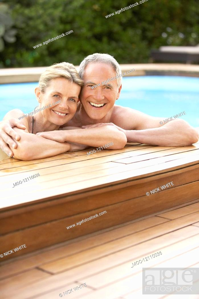 Stock Photo: Middle-aged couple standing in pool at edge portrait.