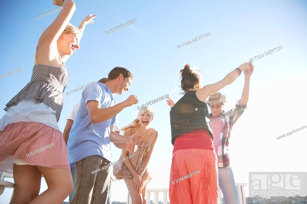 Stock Photo: Friends dancing on rooftop.