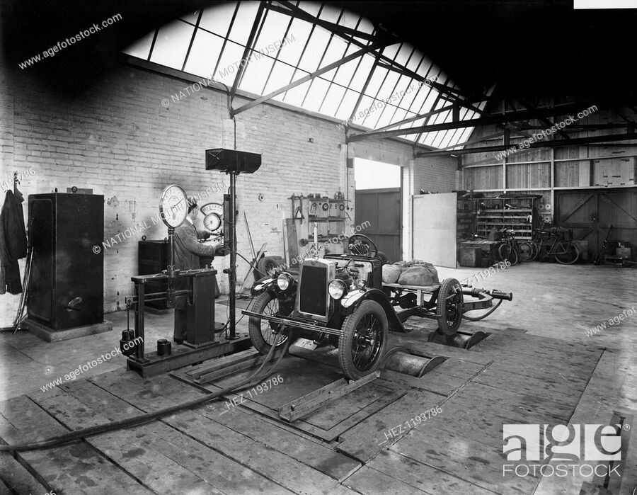 Stock Photo: Morris Minor on test, Cowley, Oxfordshire, c1930. A man testing a chassis in a garage.