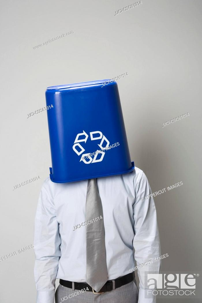 Stock Photo: Businessman with recycling bin over head.