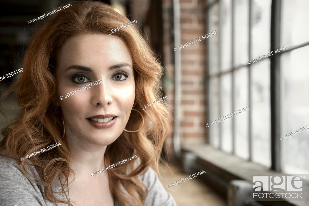 Stock Photo: A portrait of a pretty 37 year old redheaded woman smiling directly at the camera.