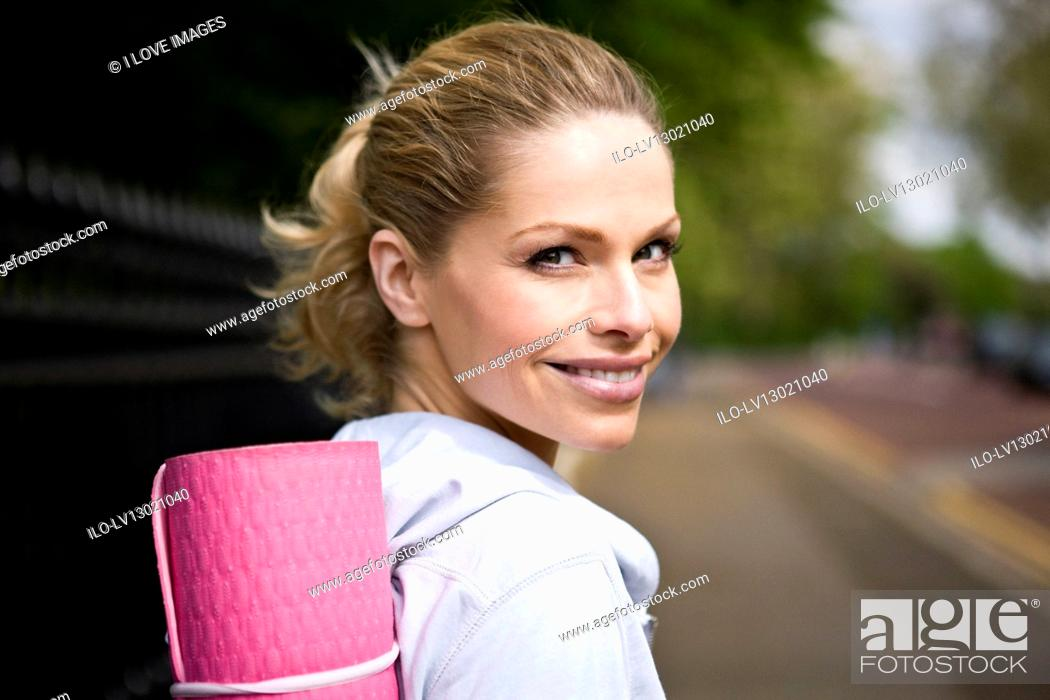 Stock Photo: Portrait of a mid adult woman carrying a yoga mat.