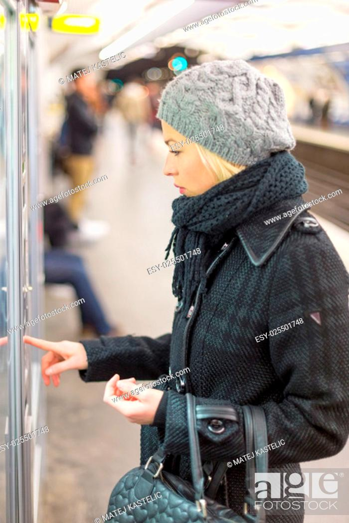 Stock Photo: Casually dressed woman wearing winter coat, buying metro ticket at the ticket vending machine. Urban transport.