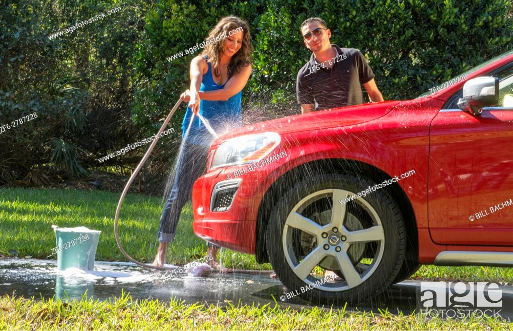 Stock Photo: Couple wash car at home hispanic couple outside in sun red car fun together love Model Released, MR-12, MR-15.