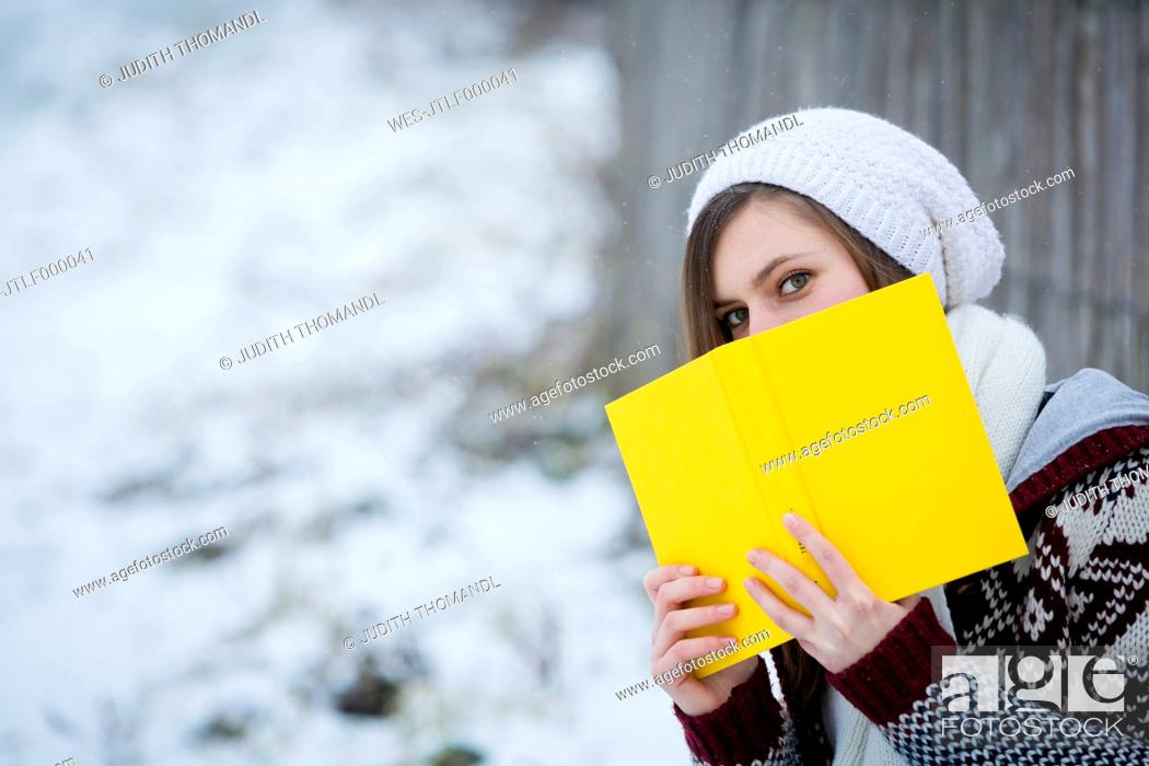 Stock Photo: Young woman hiding behind yellow book.