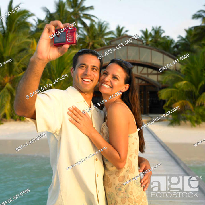 Stock Photo: Couple taking pictures of themselves on a pier.