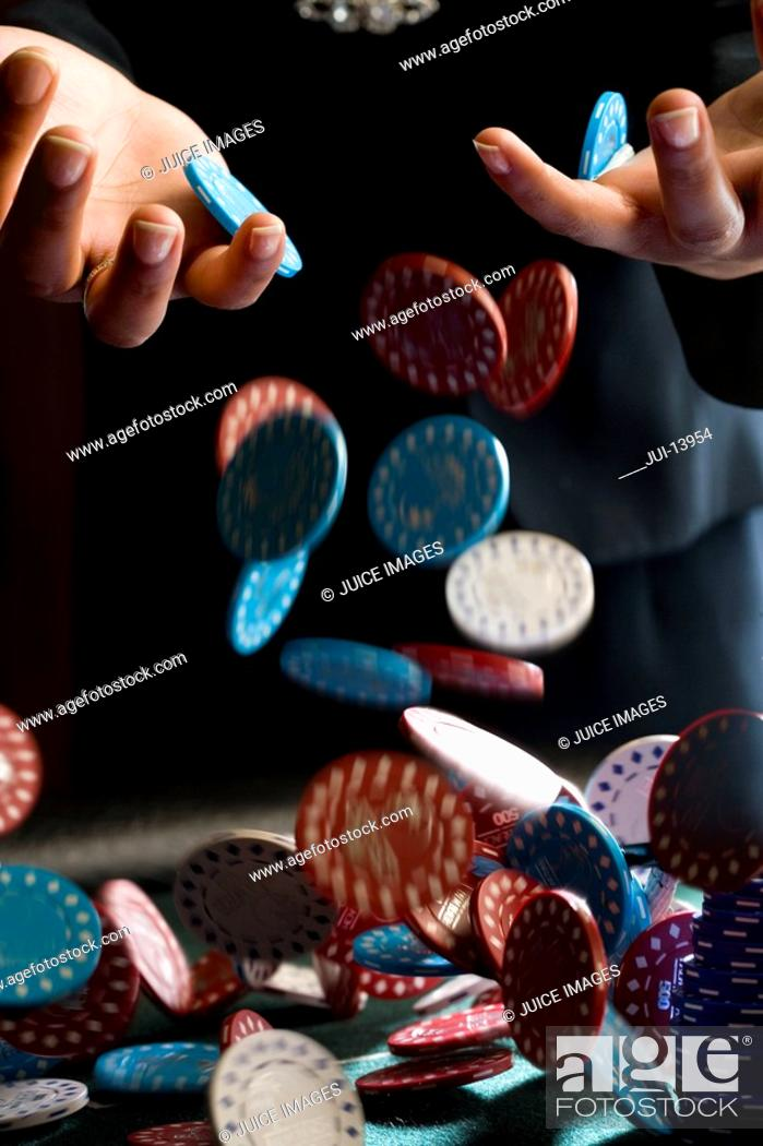 Stock Photo: Woman dropping gambling chips on table, close-up of chips falling.