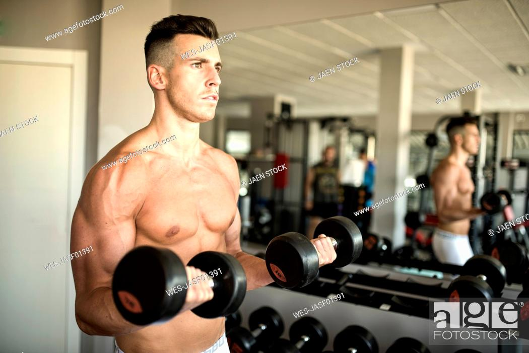 Stock Photo: Man lifting weights training biceps in gym.