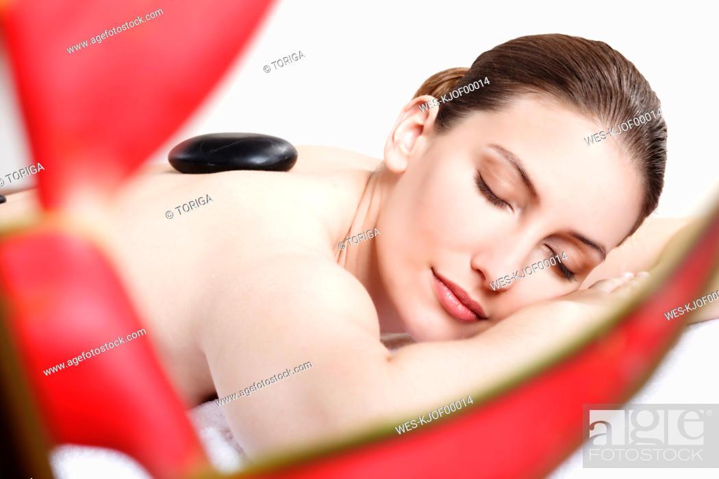Stock Photo: Woman having a hot stone treatment, eyes closed.