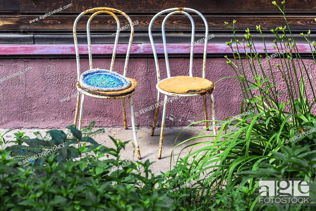 Stock Photo: Two old metal chairs stand against the wall of a residential building close.