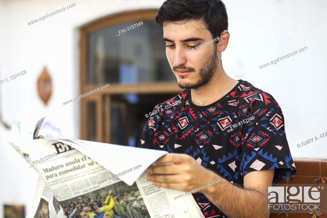 Imagen: Young man reads newspaper at outdoor cafe, Salobreña, Spain.