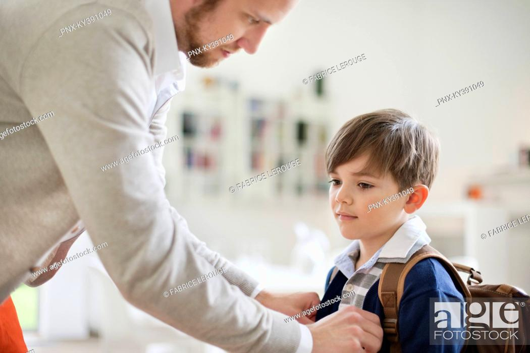 Stock Photo: Man preparing his son for school.