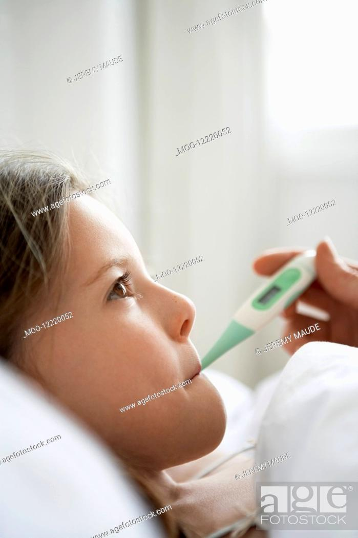 Stock Photo: Mother checking temperature of daughter in bed close up of daughter.