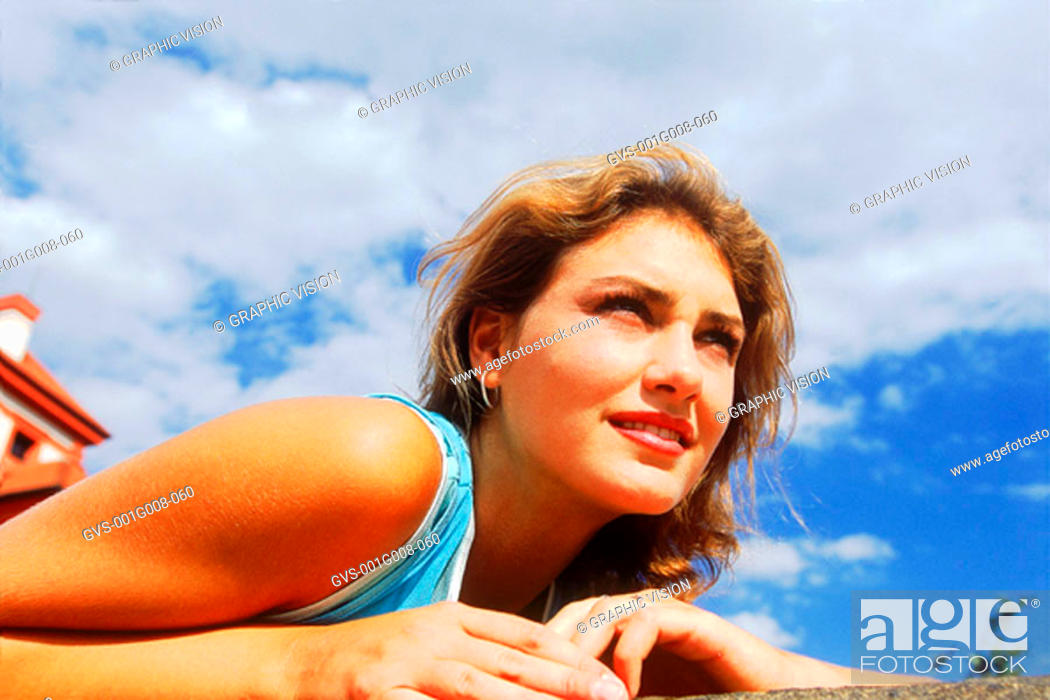 Stock Photo: Low angle view of a young woman leaning forward.