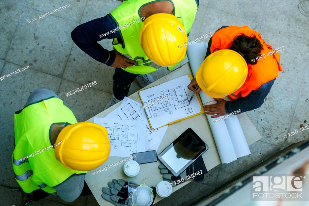 Stock Photo: Woman and two men in workwear discussing construction plan.