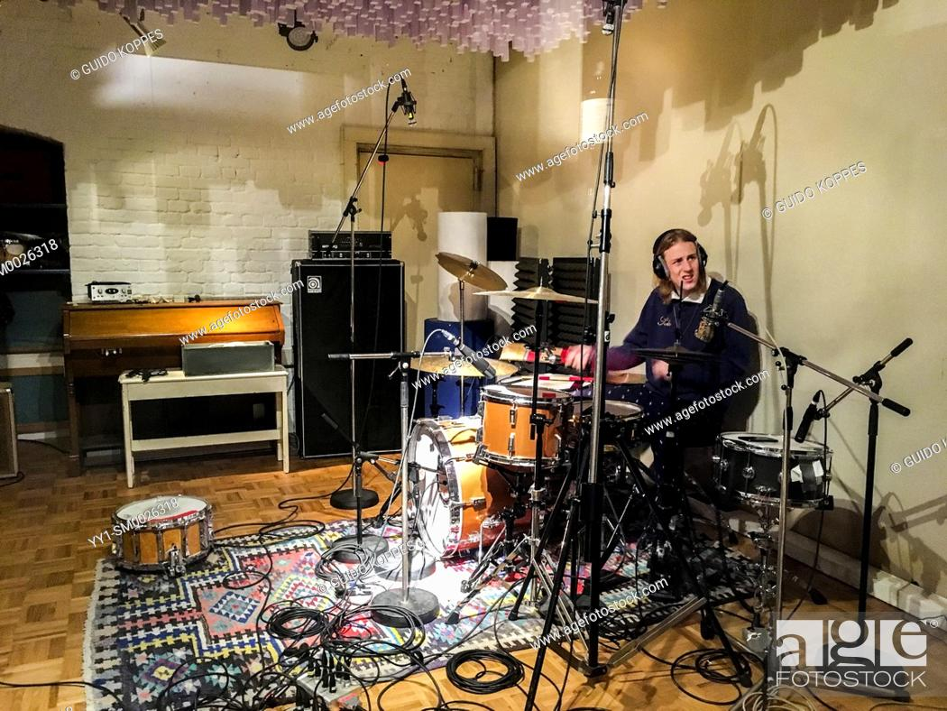 Imagen: Berlin, Germany. Music student Lucas drumming away, recording beats and sounds inside a professional music recording studio.